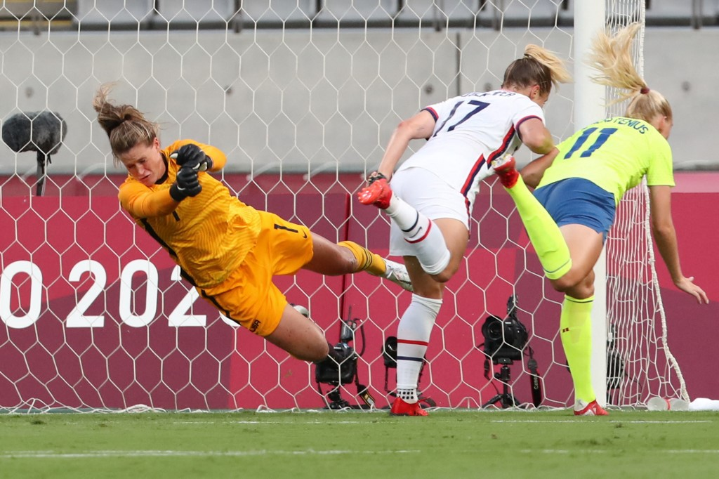 Sweden's forward Stina Blackstenius (right) shoots a header to open the scoring past USA's goalkeeper Alyssa Naeher (left) during the Tokyo 2020 Olympic Games women's group G first round football match at the Tokyo Stadium in Tokyo on July 21, 2021. — A