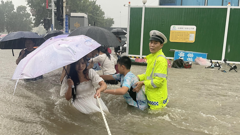 A traffic police officer guides residents to cross a flooded road with a rope during heavy rainfall in Zhengzhou, Henan province, China July 20, 2021. — Reuters pic