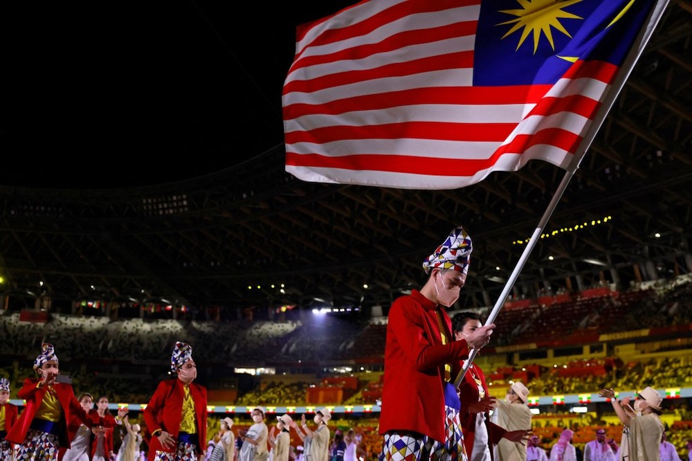 Lee Zii Jia (left) is seen carrying the Malaysian flag for the country's Olympic delegation. — AFP pic