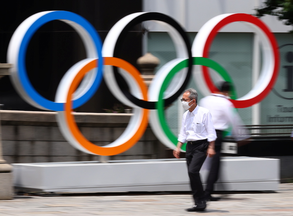 A man wearing a protective mask, amid the coronavirus disease (Covid-19) outbreak, walks past an Olympic Ring installation in Tokyo, Japan, July 28, 2021. — Reuters pic