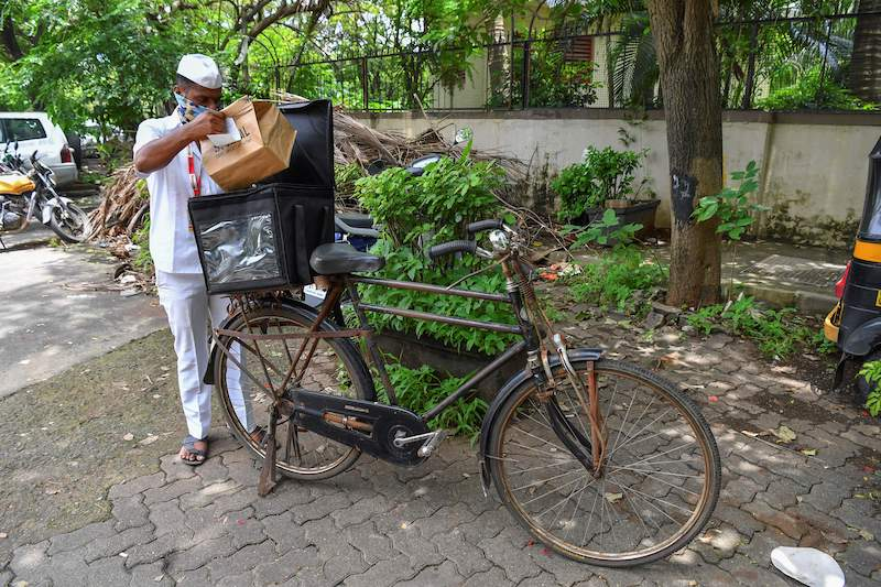 'Dabbawala', Mumbai's famed cycle-borne tiffin delivery men, Pandurang Jadhav prepares to deliver an order after collecting it from a restaurant in Mumbai June 22, 2021. — AFP pic