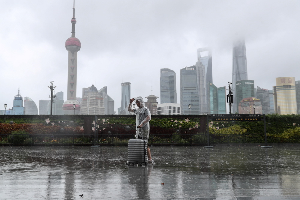 A man with luggage walks in the rain on The Bund as Typhoon In-fa approaches Shanghai, China July 25, 2021. — cnsphoto via Reuters