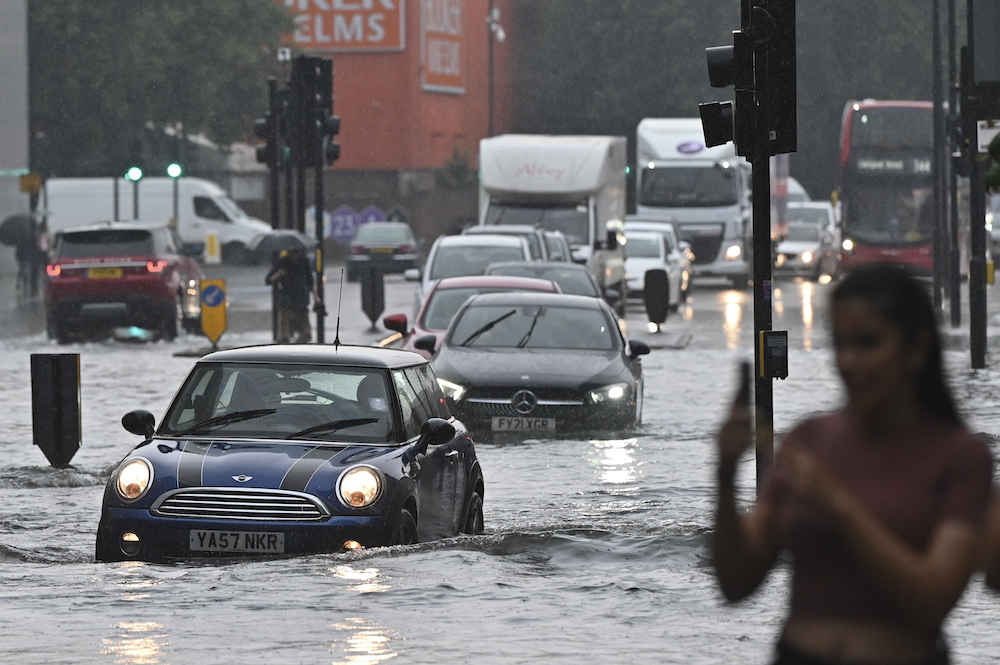 Cars are driven through deep water on a flooded road in The Nine Elms district of London on July 25, 2021 during heavy rain. — AFP pic