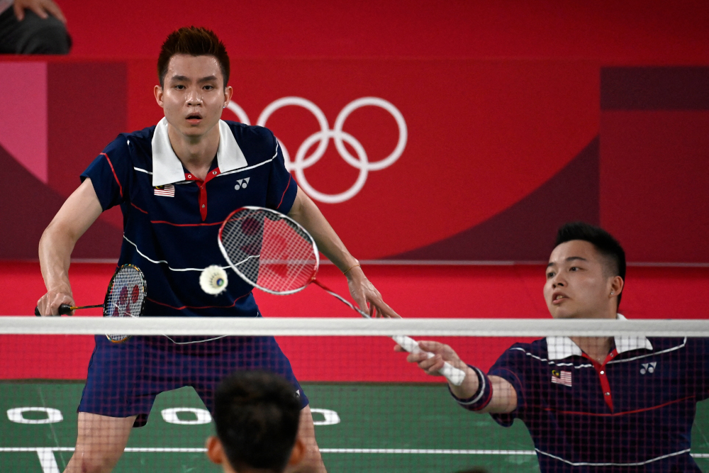 Malaysia's Aaron Chia hits a shot next to Soh Wooi Yik in their men's doubles badminton semi-final match against China's Liu Yuchen and Li Junhui at the Musashino Forest Sports Plaza in Tokyo July 30, 2021. — AFP pic
