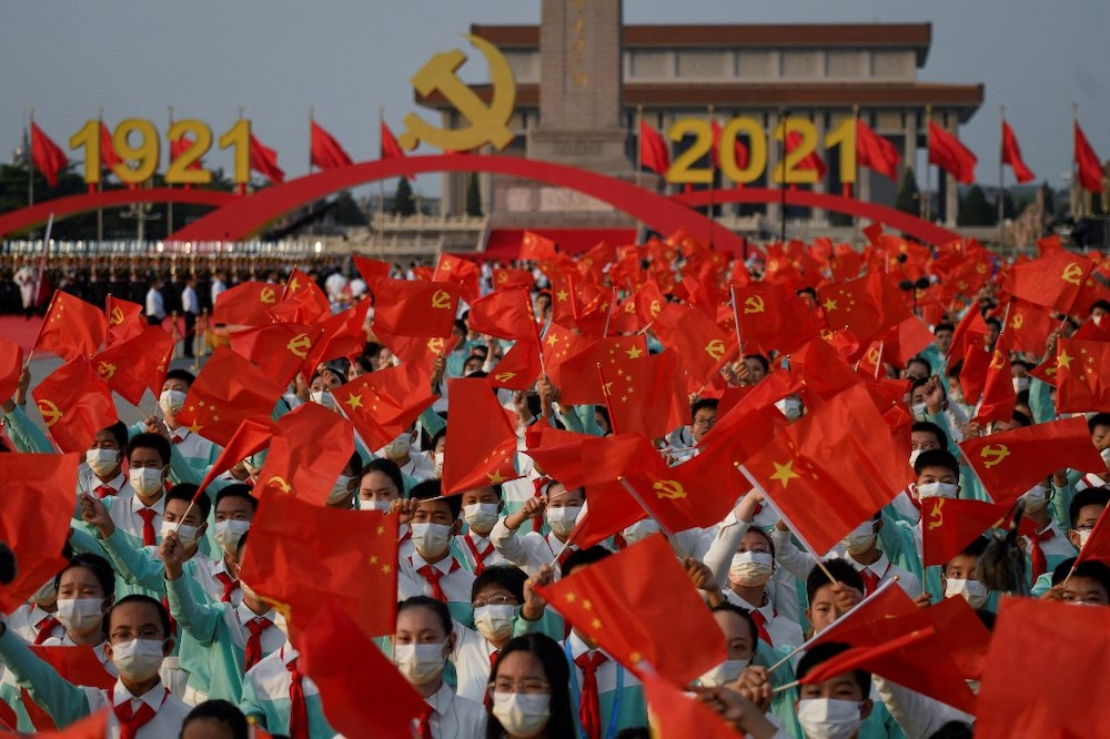 Students wave flags of China and the Communist Party of China before celebrations in Beijing on July 1, 2021, to mark the 100th anniversary of the founding of the Communist Party of China. — AFP pic