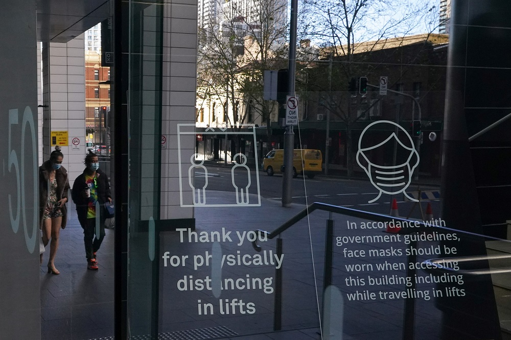 People wearing protective face masks walk past signs in the lobby of a City Centre building outlining public health guidelines during a lockdown to curb the spread of Covid-19 outbreak in Sydney July 21, 2021. ― Reuters pic
