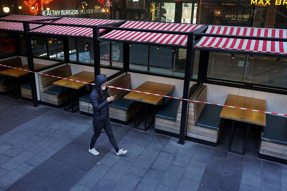 A woman wearing a protective mask walks past city centre restaurant tables closed to seating in accordance with public health regulations during a lockdown to curb the spread of Covid-19 in Sydney July 5, 2021. ― Reuters pic