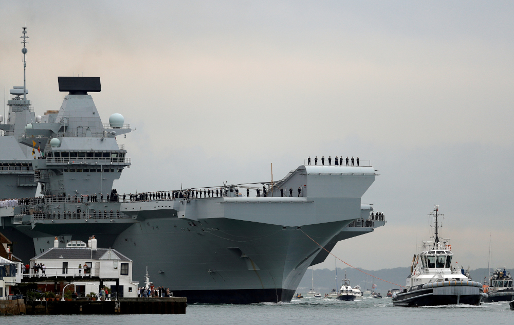 Royal Navy aircraft carrier, HMS Queen Elizabeth, is towed by tugs as it arrives at Portsmouth Naval base, Britain August 16, 2017. — Reuters pic