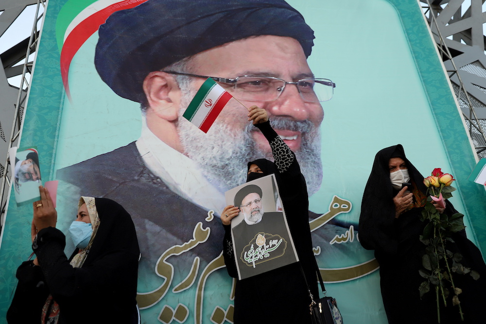 A supporter of Ebrahim Raisi displays his portrait during a celebratory rally for his presidential election victory in Tehran, Iran June 19, 2021. — Reuters pic