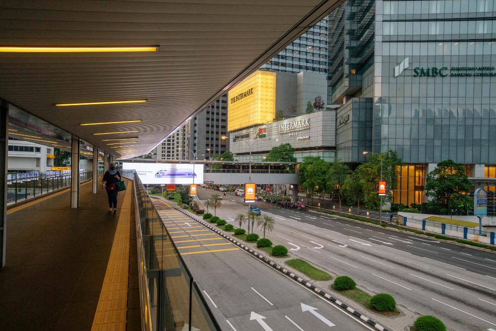 A pedestrian walks along an elevated walkway in Kuala Lumpur July 1, 2021. — Picture by Firdaus Latif