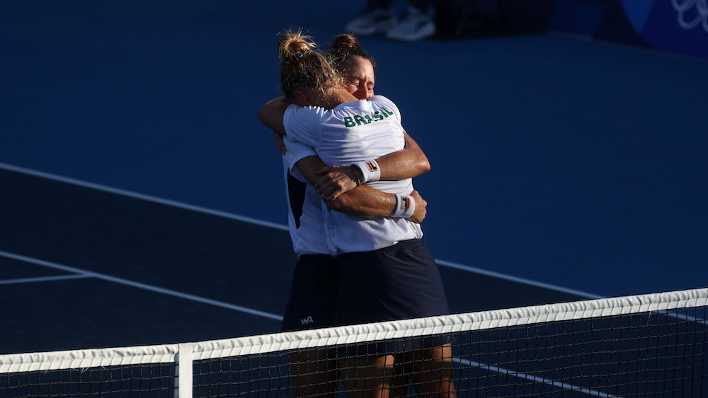 Laura Pigossi of Brazil and Luisa Stefani of Brazil celebrate after winning their bronze medal match against Elena Vesnina of the Russian Olympic Committee and Veronika Kudermetova of the Russian Olympic Committee at the Women's tennis Doubles at the Ar