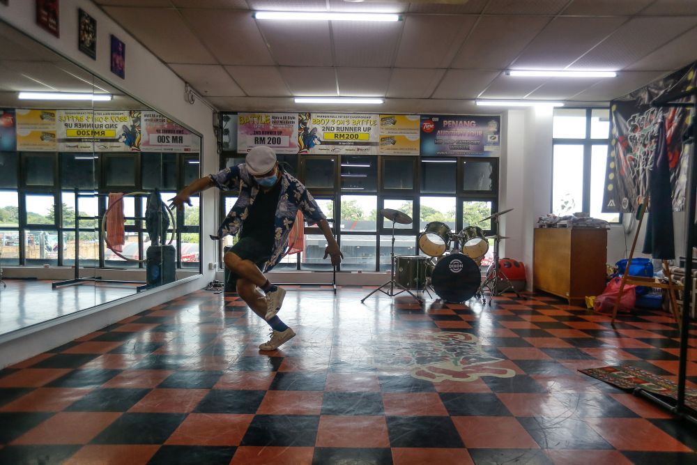 Streetdancer Low Sawming busts a move at his dance studio in Bagan Jermal during an interview with Malay Mail July 9, 2021.