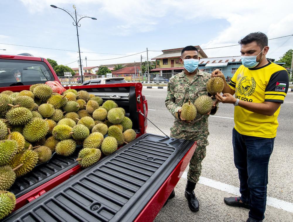 MZ Gold chief executive officer Murtadhatumizi Mustapha distributes 1200kg tonnes of durians at drive-through giveaway in Pasir Pekan, Kota Bharu, July 24, 2021. — Bernama pic