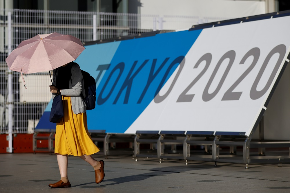 A woman walks past Tokyo 2020 Olympic Games signage at the Main Press Centre in Tokyo, Japan July 16, 2021. ― Reuters pic