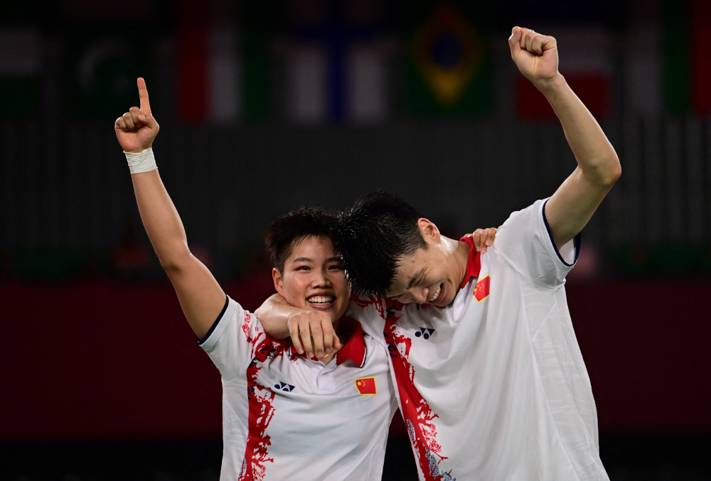 China's Huang Dongping and Wang Yilyu (right) celebrate winning the mixed doubles badminton final match against China's Zheng Siwei and Huang Yaqiong at the Musashino Forest Sports Plaza in Tokyo July 30, 2021. — AFP pic