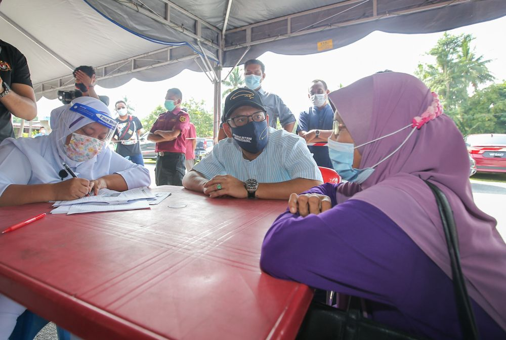 Datuk Seri Ahmad Faizal Azumu speaks to residents of Kampung Sungai Lah during a visit to the vaccination centre in Chenderiang, Tapah. – Picture by Farhan Najib