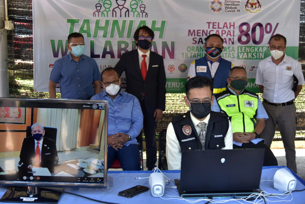 Federal Territories Minister Tan Sri Annuar Musa in a live virtual session with Labuan Health director Dr Ismuni Bohari (front) and Labuan District Disaster Management Committee chairman Rithuan Ismail in Labuan, July 27, 2021. — Bernama pic