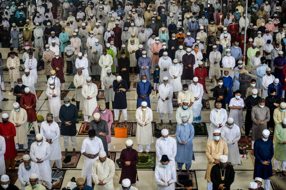 People offer prayers to mark the start of the Muslim festival Aidiladha in Dhaka July 21, 2021. — AFP pic