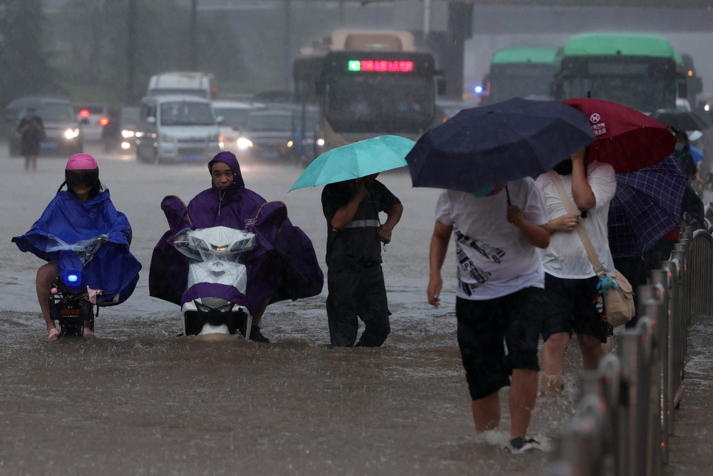 This photo taken July 20, 2021 shows people wading through flood waters along a street following heavy rains in Zhengzhou in China's central Henan province. — AFP pic
