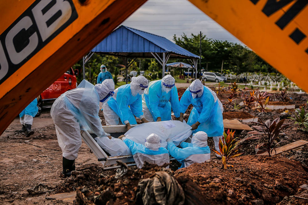 Health workers in personal protective equipment bury the body of a Covid-19 victim at the Muslim cemetery in Section 21, Shah Alam, July 10, 2021. ― Picture by Hari Anggara