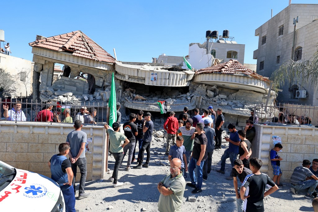 Palestinians gather outside a building that belonged to Montasser Shalabi, after it was demolished by Israeli forces in the village of Turmus'ayya near Ramallah in the occupied West Bank on July 8, 2021. — AFP pic