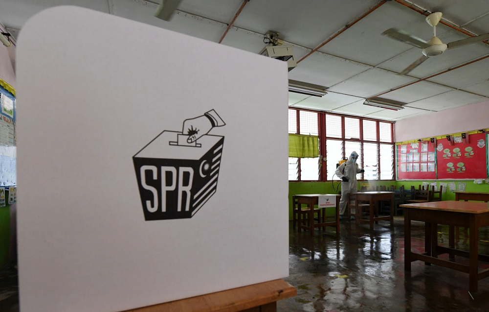 A worker conducting disinfection works in a school classroom, which served as one of the polling stations during the snap Sabah state election last year. ― Bernama file pic