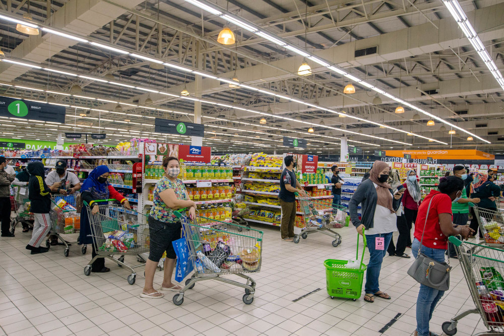 People buy groceries at a supermarket ahead of the enhanced movement control order (EMCO) in Gombak, Selangor July 2, 2021. — Picture by Firdaus Latif