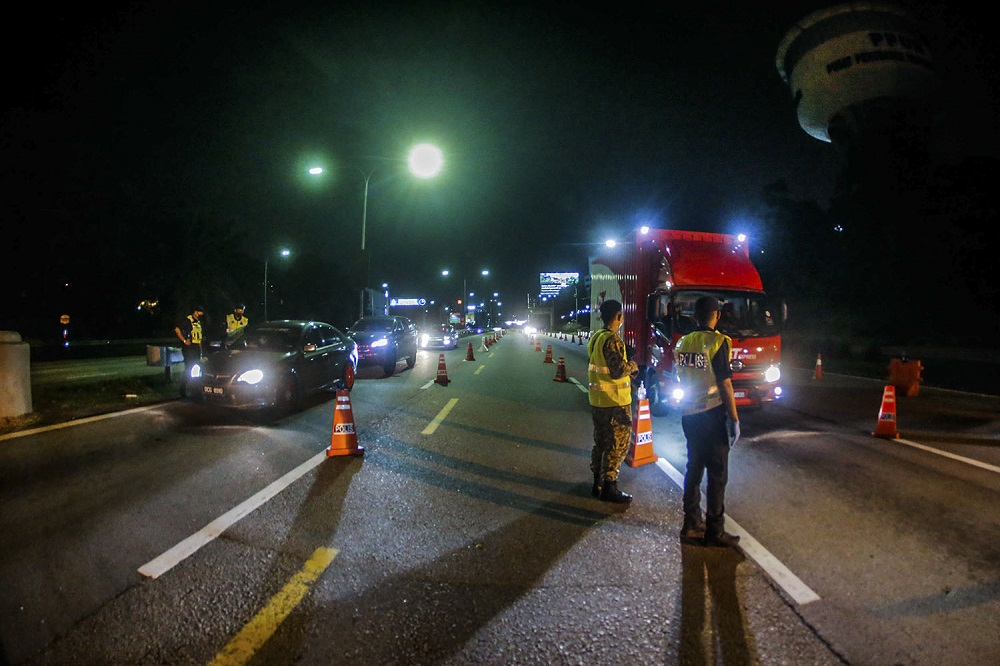 Police and army personnel man a roadblock at KM34 of the Federal Highway in Kuala Lumpur June 2, 2021. ― Picture by Hari Anggara