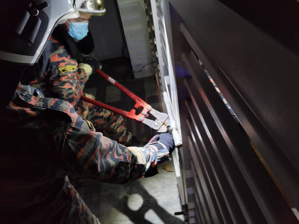 Firemen attempting to break the gate's lock in a house in Bandar Seri Alam in Pasir Gudang after a woman was locked-in with 27 of her pet cats July 6, 2021. — Picture courtesy of the Pasir Gudang Fire and Rescue Station