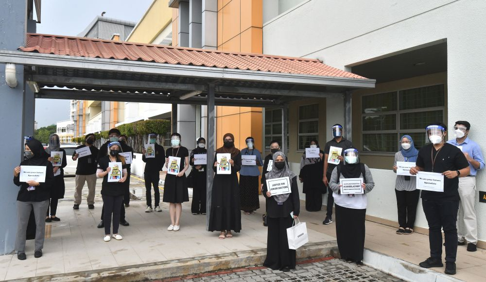 Contract doctors hold aloft placards demanding equal treatment as they go on strike at the Putrajaya Hospital July 26, 2021.