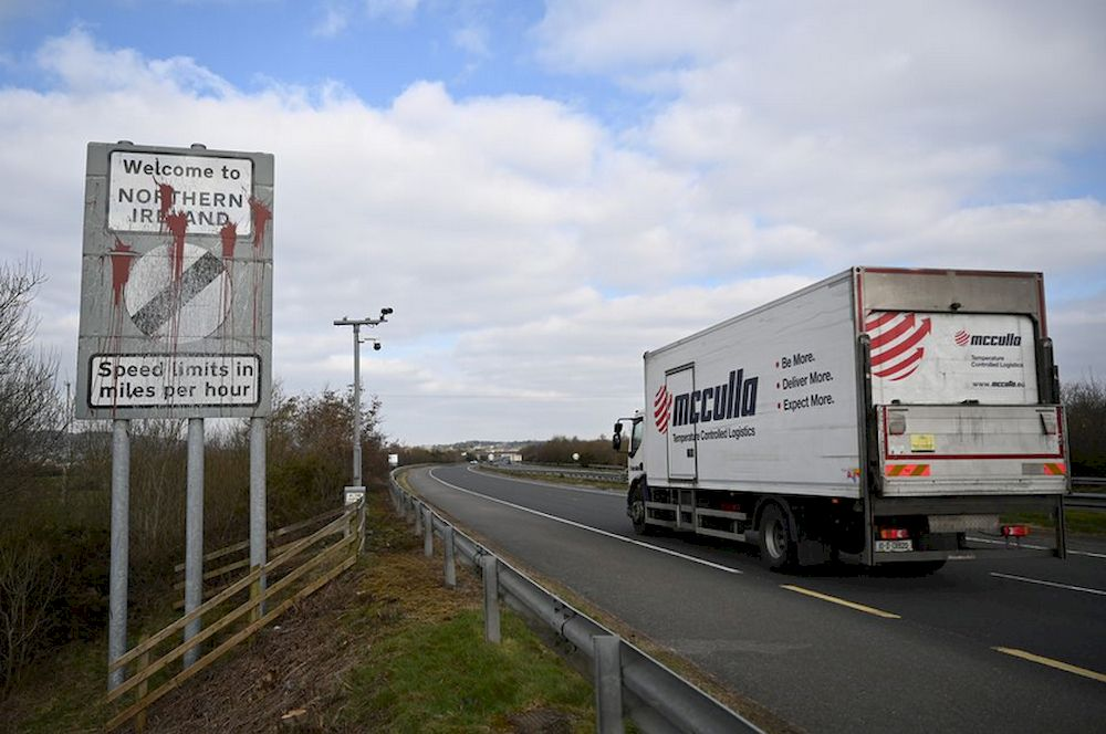 A truck drives past a defaced 'Welcome to Northern Ireland' sign on the Ireland and N. Ireland border reminding motorists that the speed limits will change from kilometres per hour to miles per hour on the border in Carrickcarnan, Ireland, March 6, 20