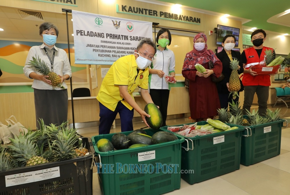 Dr Sim (second left) picks a 'Black Lady' watermelon to be distributed to the frontliners and those in need.  —  Picture by Chimon Upon via Borneo Post Online
