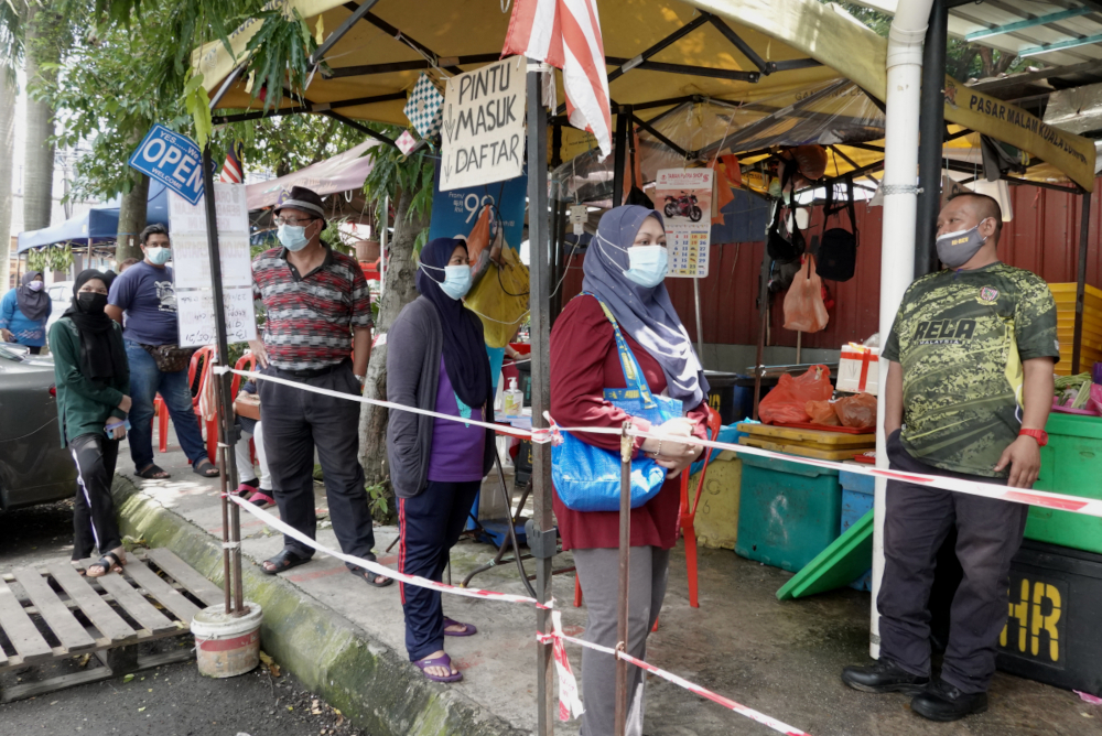 Residents of Kerinchi PPR stand in line to get provisions, July 2, 2021. — Picture by Miera Zulyana