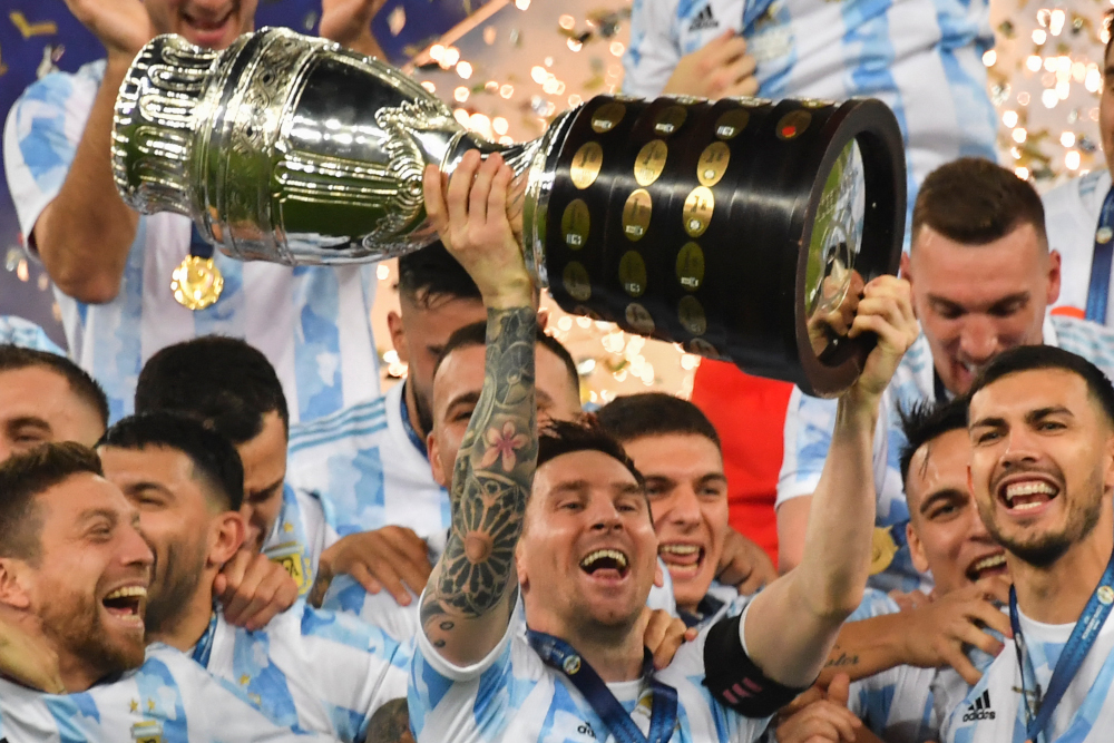 Argentina's Lionel Messi holds the trophy as he celebrates on the podium with teammates after winning the Conmebol 2021 Copa America football tournament final match against Brazil at Maracana Stadium in Rio de Janeiro, Brazil, July 10, 2021. — AFP pic