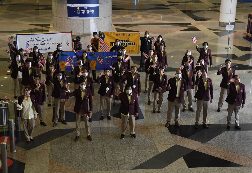 Malaysian athletes are pictured at the Kuala Lumpur International Airport wave goodbye before leaving for the 2020 Tokyo Olympic Games on July 17, 2021. — Bernama
