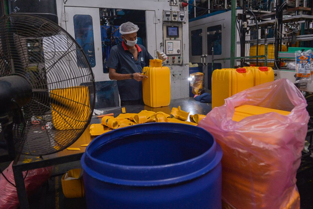 A worker is seen at his station at Mapo Industries Sdn Bhd's plastic container manufacturing plant in Port Klang July 8, 2021. — Picture by Miera Zulyana