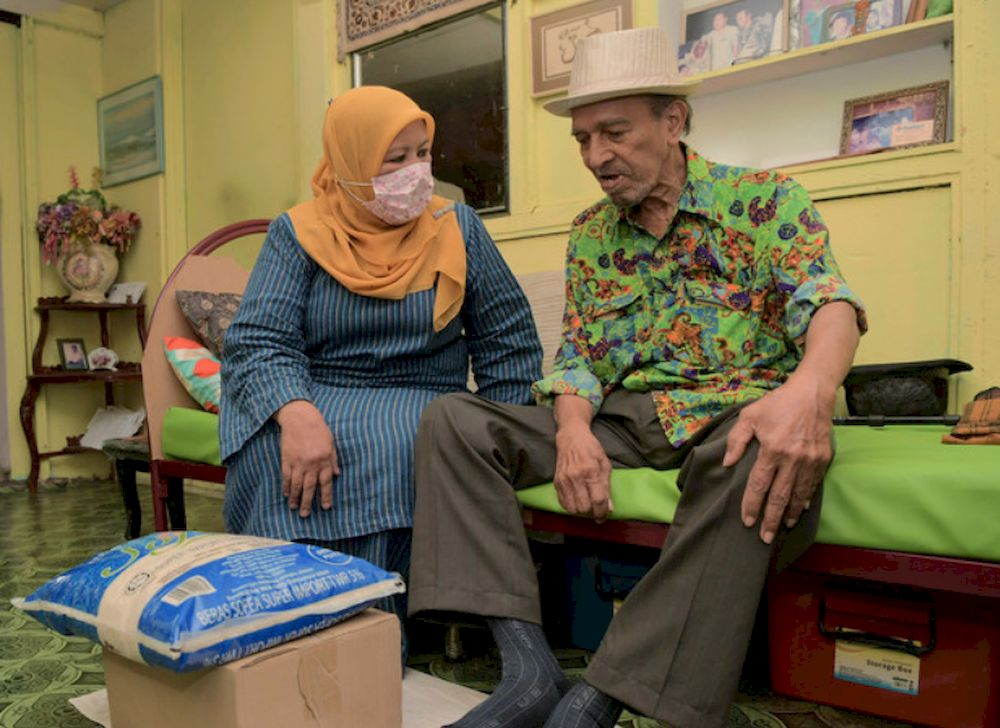 File picture shows Johor Women, Family and Community exco, Zaiton Ismail (left) presenting a basket of food and money to veteran film actor and comedian, Abdul Rashid Yahya, better known as Mat Sentol at his home in Larkin April 20, 2021. — Bernama pic