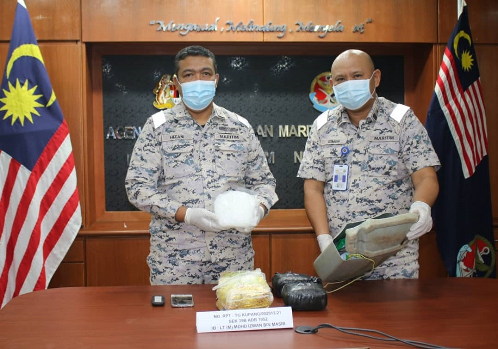 Johor MMEA director First Maritime Admiral Nurul Hizam Zakaria (left) showing the seized syabu illicit drugs by the MMEA team at the waters off Pulau Merambong yesterday July 22, 2021. — Picture courtesy of the Johor Malaysian Maritime Enforcement Agency (MMEA)
