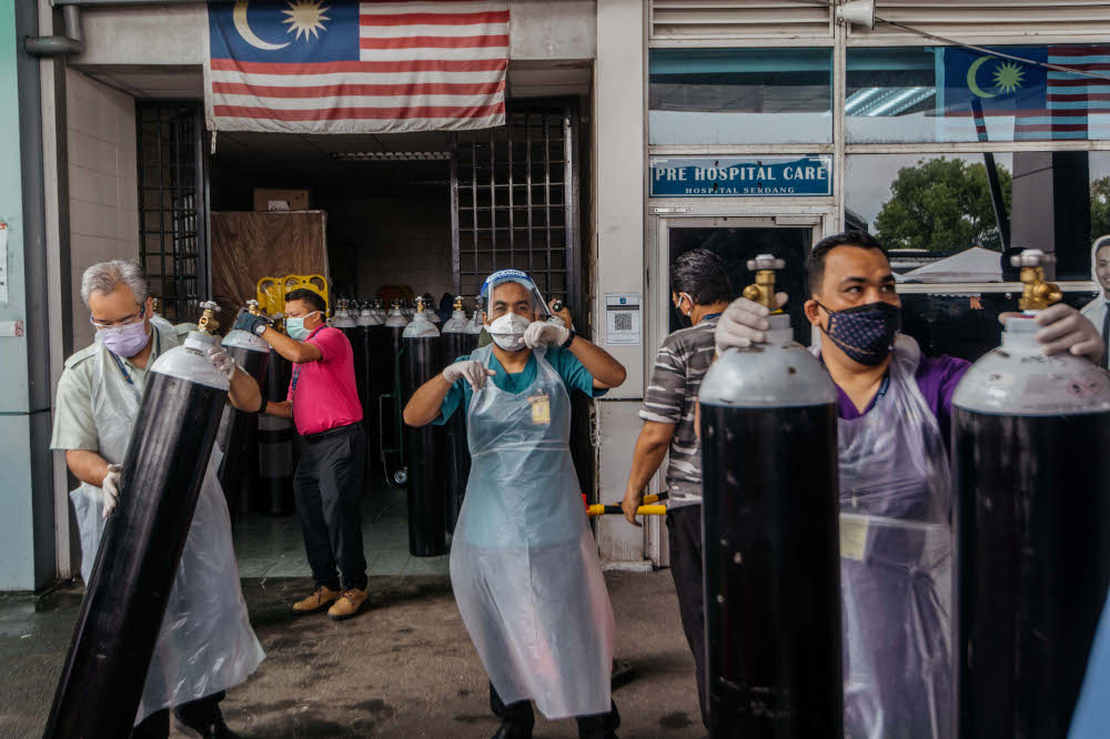 Workers arrange medical oxygen cylinders to be sent to the Covid-19 Low-Risk Quarantine and Treatment Centre (PKRC) at the Malaysia Agriculture Expo Park (MAEPS) at Hospital Serdang July 26, 2021. — Picture by Shafwan Zaidon