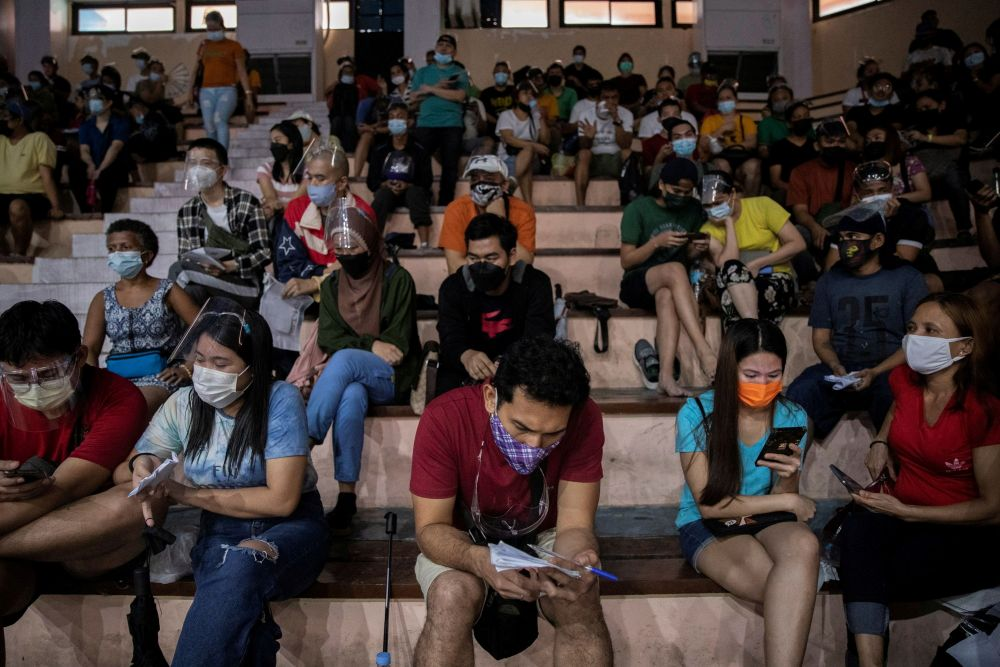 Filipinos use their smartphones while queuing for free vaccination against the coronavirus disease at San Andres Sports Complex in Manila July 21, 2021. — Reuters pic