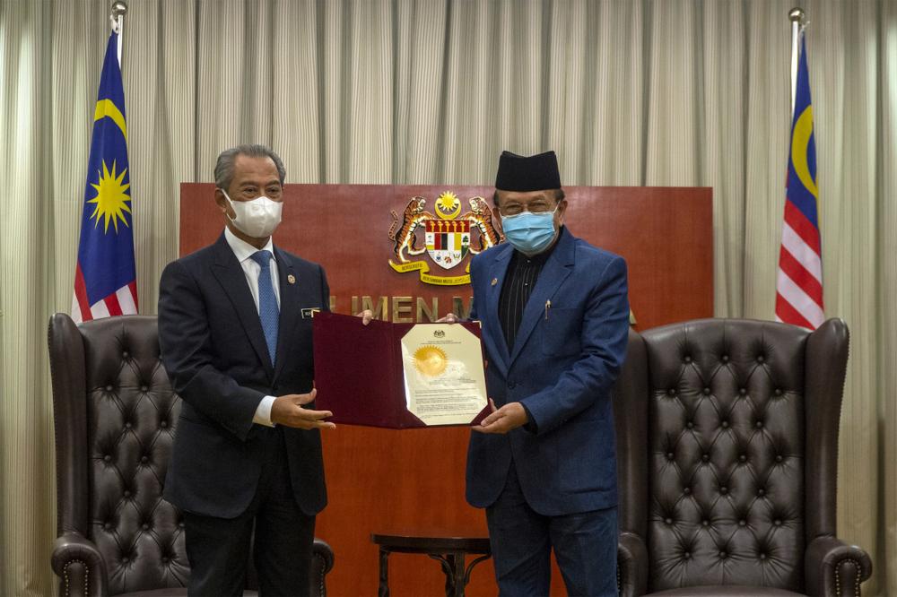 Prime Minister Tan Sri Muhyiddin Yassin presents the letter of appointment to Tan Sri Rais Yatim in Parliament, July 26, 2021. — Bernama pic