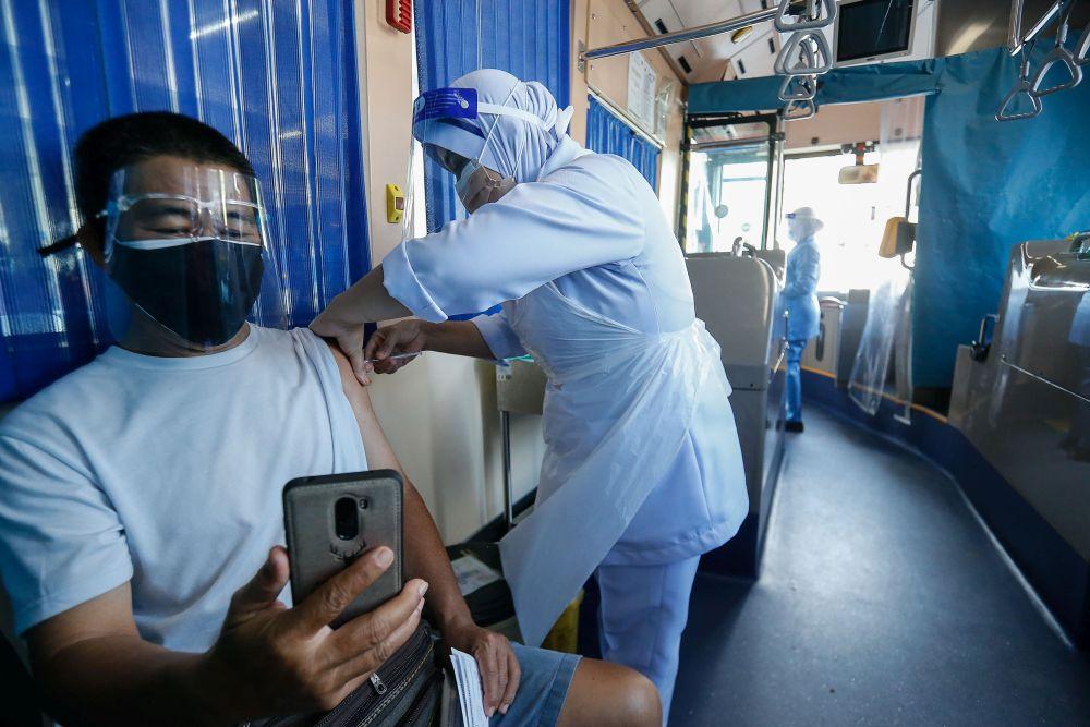 A man receives his Covid-19 jab aboard a RapidPenang bus, which doubles as a mobile vaccination centre at Sekolah Kebangsaan Pai Chai, Batu Feringghi July 28, 2021. — Picture by Sayuti Zainudin