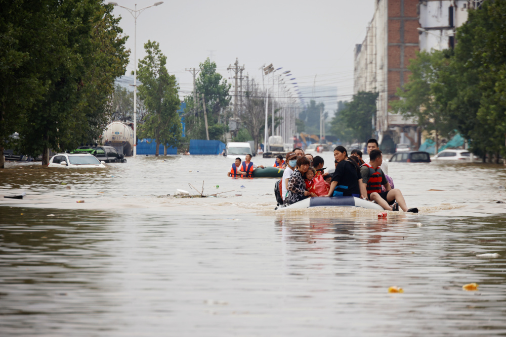 People ride a boat as they make their way through a flooded road following heavy rainfall in Zhengzhou, Henan province July 22, 2021. — Reuters pic
