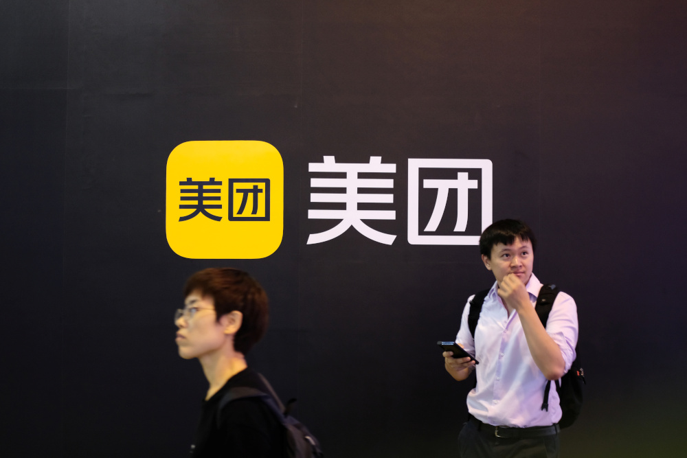 People walk past a Meituan logo at the World Artificial Intelligence Conference (WAIC) in Shanghai July 8, 2021. — Reuters pic