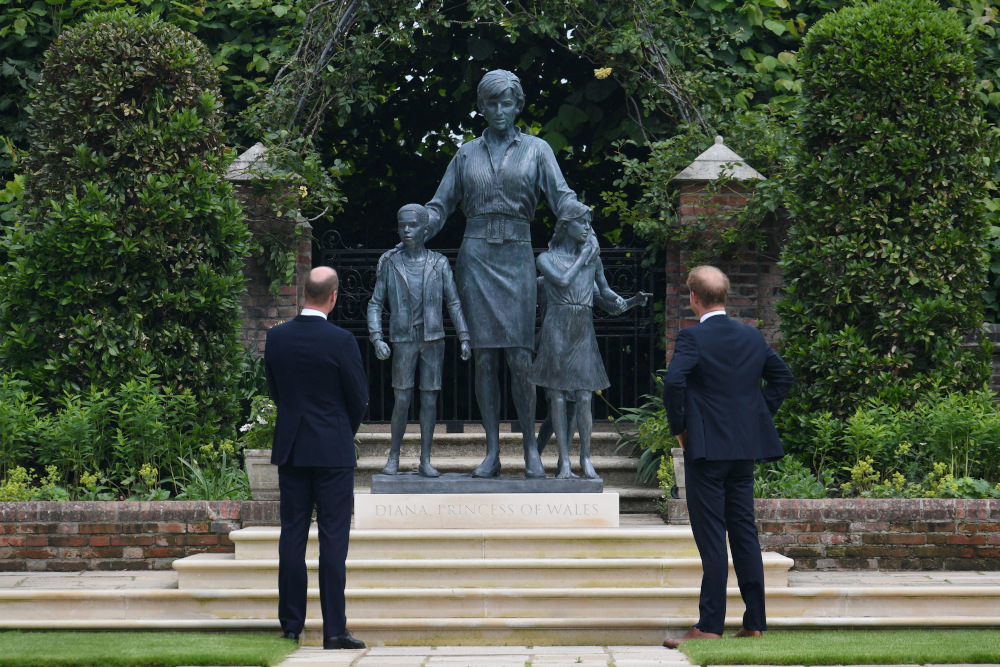 Prince William, Duke of Cambridge, and Prince Harry, Duke of Sussex, look at a statue they commissioned of their mother Diana, Princess of Wales, in the Sunken Garden at Kensington Palace, London July 1, 2021. — Dominic Lipinski/Pool pic via Reuters