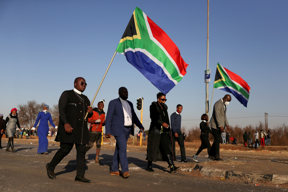 Religious leaders carrying South African flags walk near a looted shopping mall as the country deployed the army to quell unrest linked to the jailing of former South African President Jacob Zuma, in Vosloorus July 14, 2021. — Reuters pic