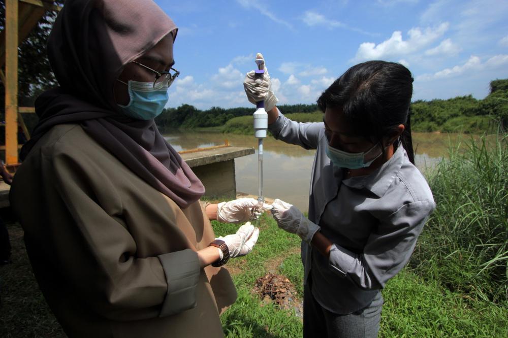 Pengurusan Air Pahang Berhad staff analyse the water quality at Sungai Pukin in Rompin, July 9, 2021. — Bernama pic