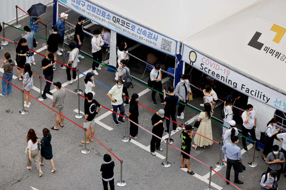 People wait in line for a Covid-19 test at a testing site which is temporarily set up at a public health centre in Seoul, South Korea, July 9, 2021. — Reuters pic