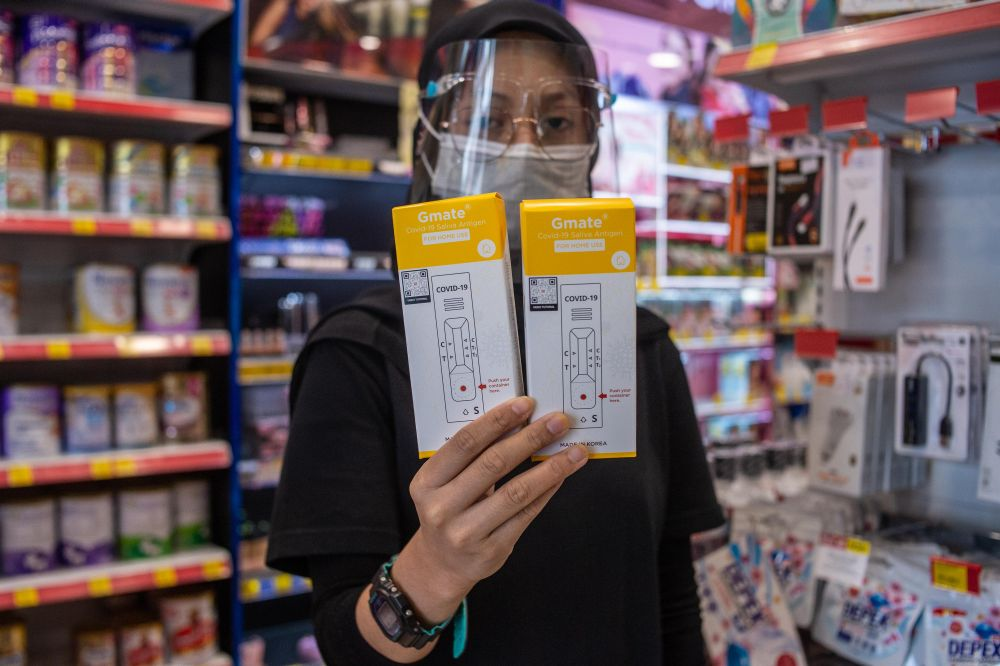 A pharmacy staff holds up the Gmate Covid-19 rapid antigen self-test kits in Subang Jaya July 28, 2021. — Pictures by Shafwan Zaidon