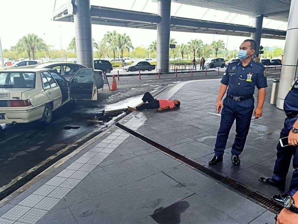 The driver of the vehicle lying down on the pavement after ramming his car into a vehicle at the front of the taxi queue at Kota Kinabalu International Airport, July 19, 2021.